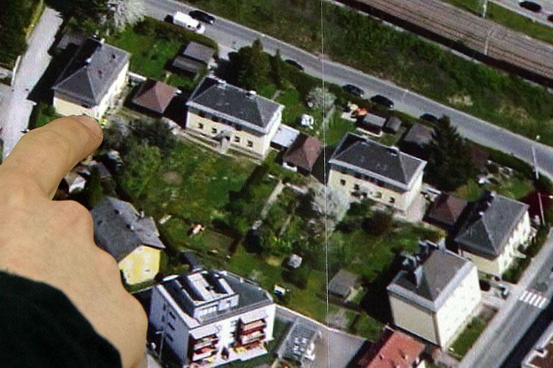 Finger zeigt auf Luftbild von alten Wohnhäusern in Salzburg Itzling