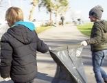 Seeputzete: Menschen mit Müllsäcken und Handschuhen sammeln Müll ein.