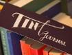 """Lesezeichen mit der Aufschrift """"Tint Journal"""" zwischen Büchern"""