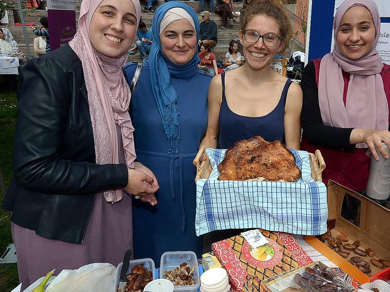 Frauen verschiedener Religionen sind an einem Stand mit Datteln und Fladenbrot zu sehen