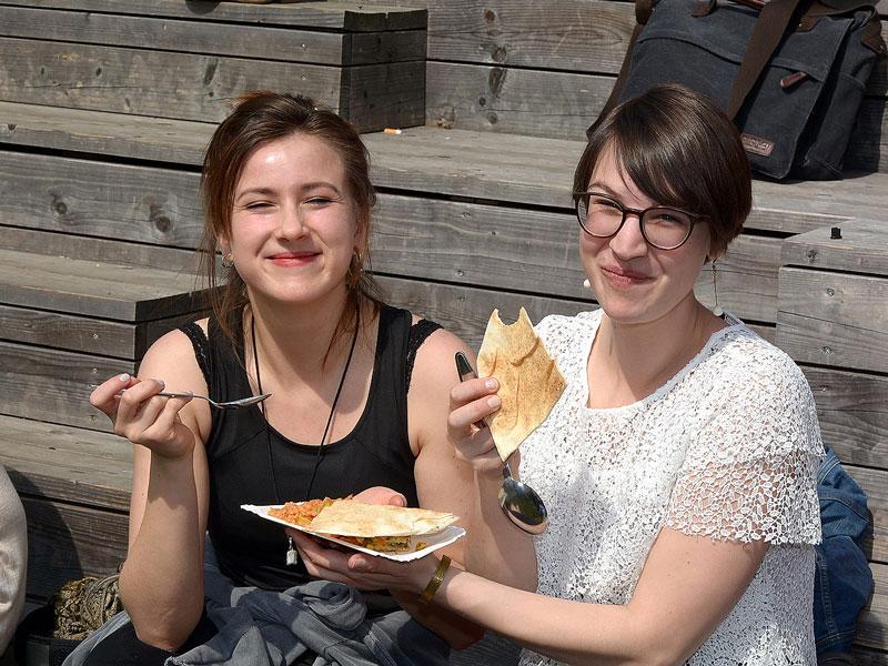 Zwei Frauen sind beim Essen der verschiedenen internationalen Fastesnspeisen zu sehen. Sie halten einen Teller mit einer Speise und ein Fladenbrot in der Hand
