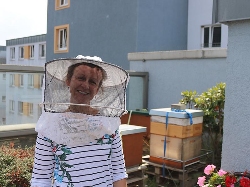 Imkerin vor Bienenstöcken