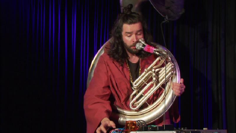 Tobias Ennemoser mit seinem Sousaphon. Er trägt ein rotes, weites Oberteil. Die Bühne ist dunkel, ein Spotlight ist auf den Künstler gerichtet, vor ihm steht ein Tisch mit Steckleiste und Mischpult.
