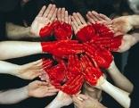 Viele Hände die ein aufgemaltes Herz anzeigen