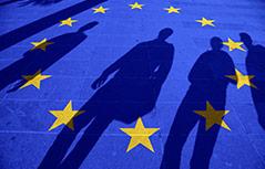 Schatten mehrerer Personen auf einer am Boden aufgemalten EU-Flagge