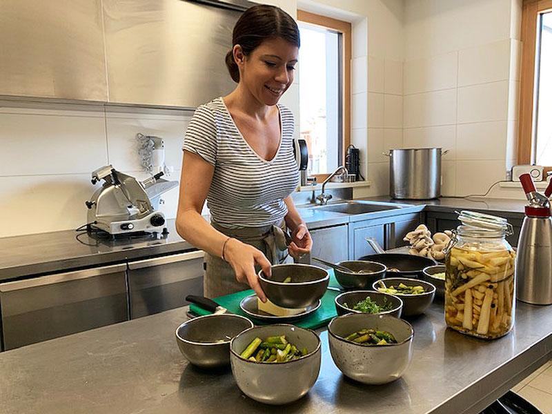 Köchin steht in der Küche und kocht Spargel