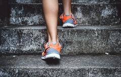 Beine in Laufschuhen, die eine Treppe hinaufsteigen