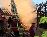 Feuerwehrleute beim Löschen eines Brandes mit Drehleiterfahrzeug