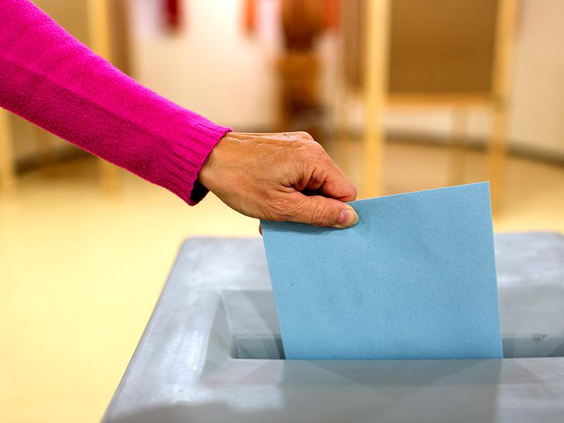 Frau gibt Kuvert in die Wahlurne