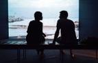 Eine Frau und ein Mann sitzen auf einer Bank vor einem großen Fenster